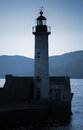Old lighthouse tower silhouette on the coast of mediterranean sea no light blue toned stylized night photo Stock Photos