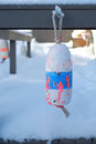 An old lobster buoy tied to a deck railing and snow covered on maine home Stock Photography