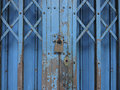Old lock on blue rusty iron gate Royalty Free Stock Photo