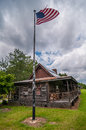 Old log cabin and american flag flying over on a pole Stock Photography
