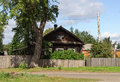 Old log house with a big tree in front tall and unpainted wooden fence of him Stock Image