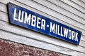 Old lumber millwork enamel sign on building wall and distressed antique advertising hanging a vintage lumberyard wood clapboard Stock Image