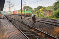 Old man dangerously crosses railway tracks in front of a goods train.