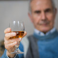 Old man drinking a glass of whiskey Stock Photography