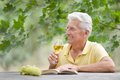 Old man drinking wine and reading a book sitting at table Royalty Free Stock Photos