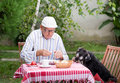 Old man eating in garden with dog Royalty Free Stock Photo
