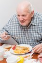 Old man eating a healthy meal Stock Images