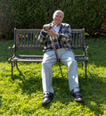 Old man enjoys sitting on a bench in his garden Royalty Free Stock Images