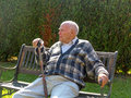 Old man enjoys sitting on a bench in his garden Royalty Free Stock Photography