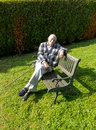 Old man enjoys sitting on a bench in his garden Stock Photo