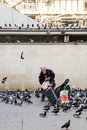 Old man feeding pigeons near the pompidou center paris france august homeless in Stock Image