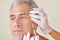Old man getting wrinkles treatment against crow s feet in beauty clinic Royalty Free Stock Photo