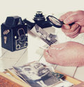 Old man hands view photos with magnifying glass from the past retro cameras on the table filtered photo Royalty Free Stock Image
