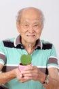 Old man hold pot green leaf heart form Stock Image