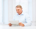 Old man at home reading newspaper oldness news leisure and happiness concept Stock Photo