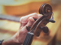 Old man luthier hands tuning aged violin Royalty Free Stock Photo