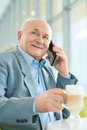 Old man making a call pleasurable time of day caring grandfather is calling his adorable granddaughter while sitting at the Royalty Free Stock Image