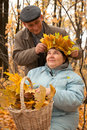 Old man put on his wife wreath of maple leaves