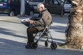 Old man reading a newspaper barcelona spain december sitting in walker in square in barcelona spain on december Royalty Free Stock Photos