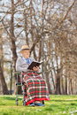 An old man reading a novel outdoors in park Stock Images