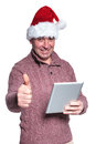 Old man with santa hat is holding a tablet and making the ok sig casual thumbs up gesture on white background Royalty Free Stock Photography