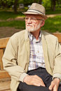 Old man sitting on park bench with hat and glasses in summer Stock Images