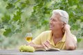 Old man sitting at a table drinking wine and reading a book Stock Photography