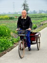 Old man smoking cigarette pipe pedals his bicycle cart along country road past fields garlic rapeseed oil flowers pengzhou china Royalty Free Stock Photos