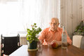 Old Man at the Table with Wine, Apple and Plant Royalty Free Stock Photo