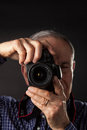 Old man taking a picture on dark background Royalty Free Stock Photos