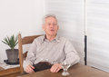 Old man talking and smiling at dining table Stock Image