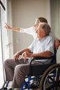 Old man on a wheelchair , nurse pointing outside Stock Image