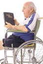 Old man in wheelchair reading a bible Stock Image