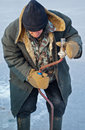 Old man on winter fishing drills ice Stock Photos