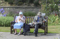 An old marriage couple sitting in the park clacton on sea essex england uk june happy elderly on bench man is reading newspaper Royalty Free Stock Photos