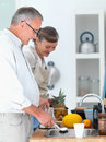 Old mature couple preparing food in the kitchen Royalty Free Stock Photos
