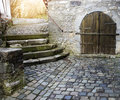 Old medieval cobblestone road and stone building Royalty Free Stock Photo