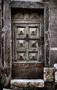 Old medieval wooden door in historic building heavy wood panel with cast iron knocker and marble steps on a an town france Stock Image
