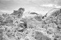 Old melting snow large pile of with mountains in the background in black and white Royalty Free Stock Photo