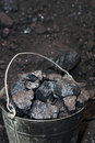 Old metal bucket full of pieces of coal Royalty Free Stock Photo