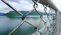 Old metal fence with mountain and lake backdrop Royalty Free Stock Photos