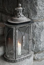 Old metal lamp with burning candle stands on stone stairs Royalty Free Stock Photography