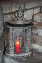 Old metal outdoor lamp with red candle burning stands on stone stairs Royalty Free Stock Images