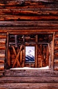 Old mining log cabin with mountian view through window this beatifully aged has a strong textures warm light and a mountain peak Royalty Free Stock Image
