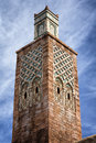 Old moroccan style brick tower against dramatic blue sky Stock Photo