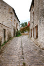 Old narrow cobblestone street in french village and with antique stone masonry traditional farm houses a rural timeless france Royalty Free Stock Image