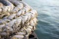 Old naval rope on a pier against blue water Stock Photos