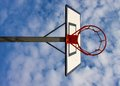 Old neglect basketball backboard with rusty hoop above street court blue cloudy sky in bckground retro filter Royalty Free Stock Image
