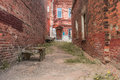 Old neglected quarter, walls of red brick destroyed form a perspective to the front door of a residential building Royalty Free Stock Photo