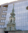 Old and new church in vienna is reflected in a modern glass facade Royalty Free Stock Photo
